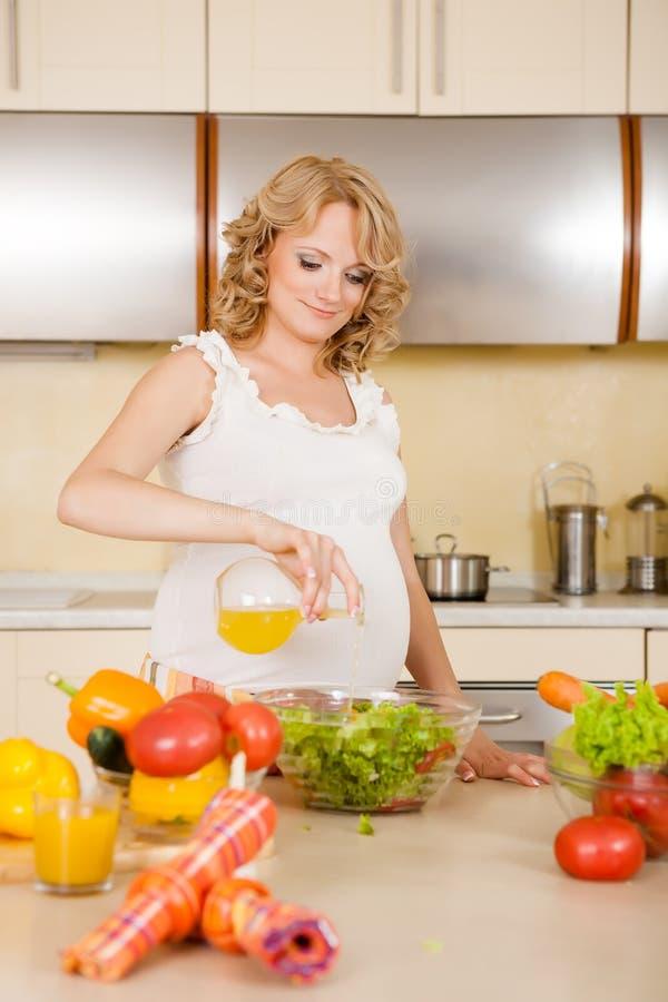 De zwangere vrouw bereidt plantaardige salade voor royalty-vrije stock fotografie