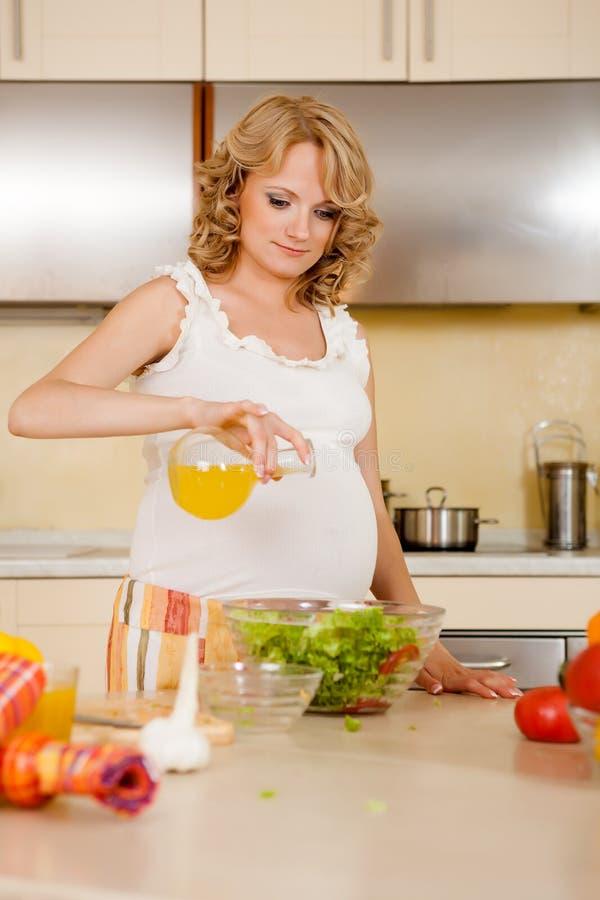 De zwangere vrouw bereidt plantaardige salade voor royalty-vrije stock afbeeldingen
