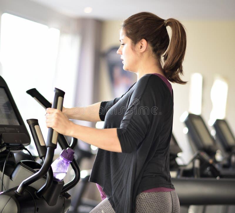 De zwangere vrouw is bezig geweest met sporten op een sportensimulator royalty-vrije stock afbeeldingen