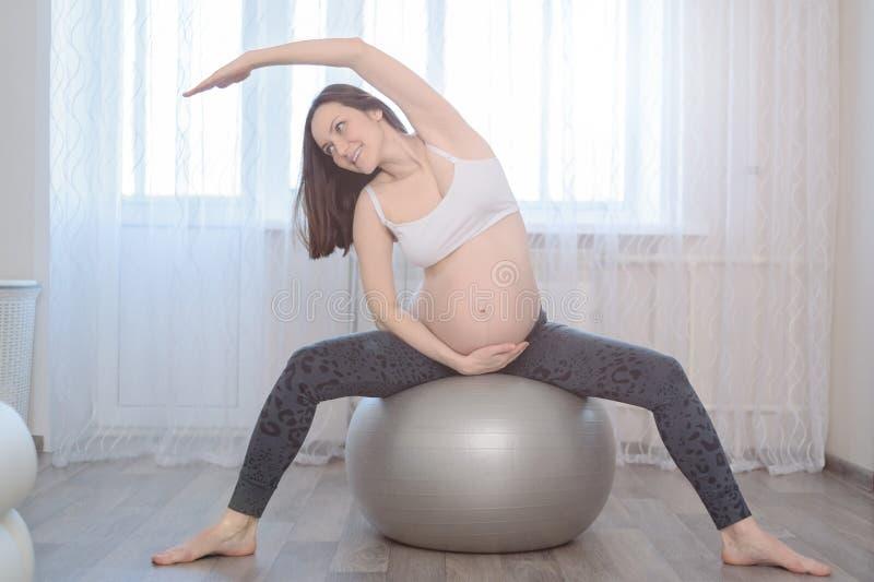 De zwangere vrouw is bezig geweest met zich het uitrekken op fitball stock afbeelding