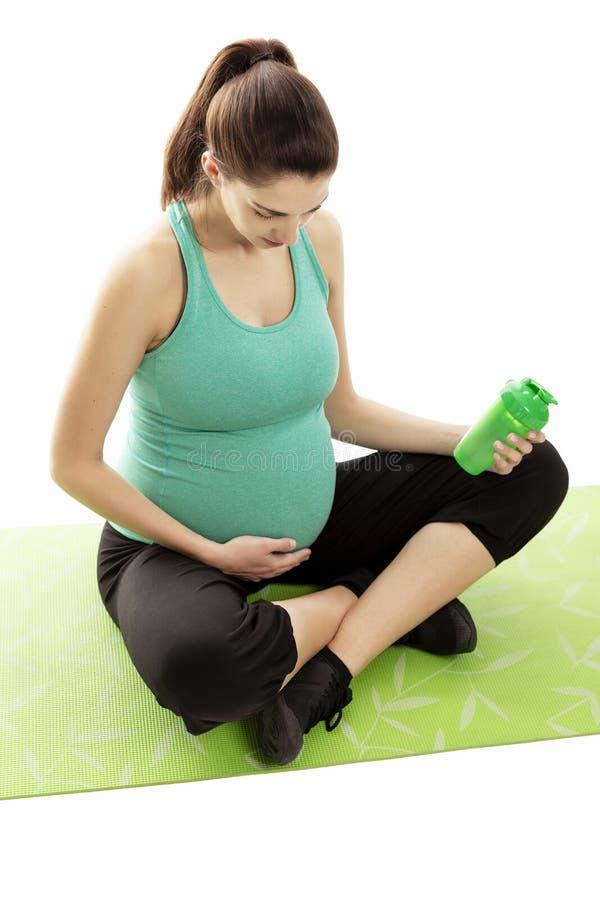 De zwangere vrouw, brunette, is bezig geweest met geschiktheid op de mat In de handen van een fles water royalty-vrije stock fotografie