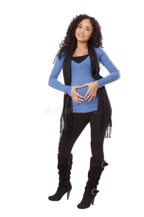 De zwangere vrouw in de winterkleding maakt een hartvorm over haar B stock fotografie