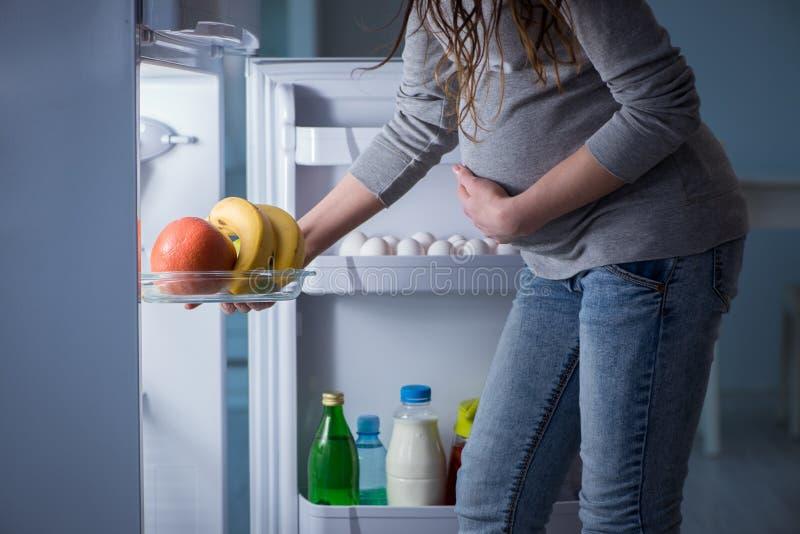 De zwangere vrouw die dichtbij koelkast voedsel en snacks zoeken bij nacht royalty-vrije stock foto