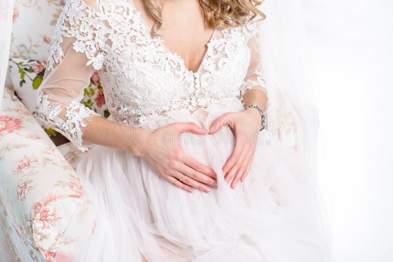 De zwangere vrouw die haar houden dient de vorm van hart op haar in is royalty-vrije stock foto's