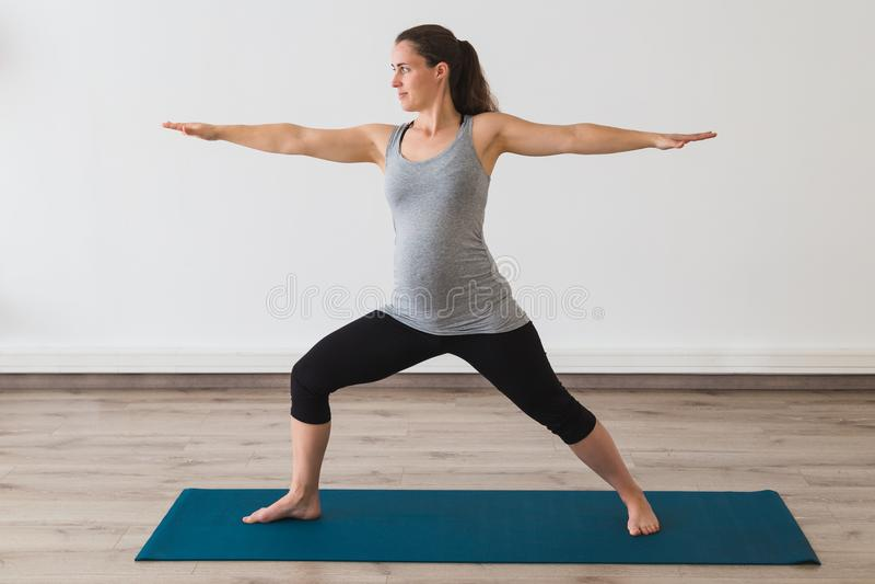 De zwangere vrouw die prenatale yoga in strijder 2 doen stelt stock foto's
