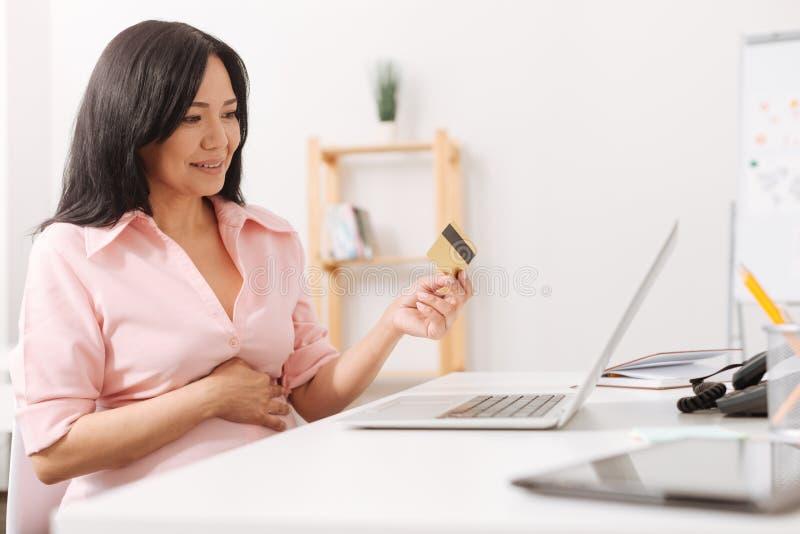De zwangere vrouw die van Nice haar creditcard houden stock afbeelding