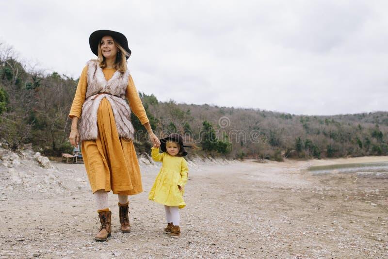 De zwangere vrouw in een gele kleding en een bruine hoed loopt met haar meisje openlucht stock afbeeldingen