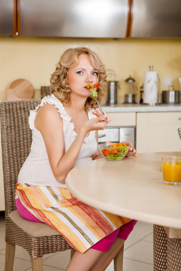 De zwangere vrouw eet thuis plantaardige salade royalty-vrije stock foto's