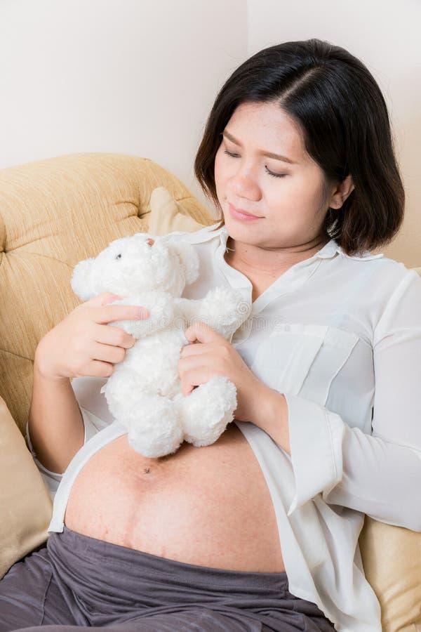 De zwangere vrouw en draagt pop spel met haar baby stock foto's