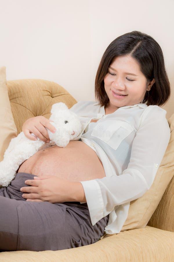 De zwangere vrouw en draagt pop spel met haar baby stock afbeelding