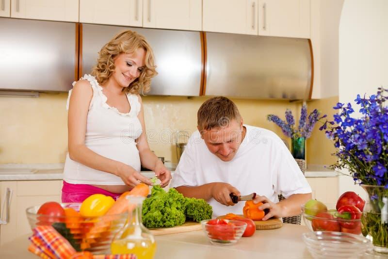 De zwangere vrouw en haar echtgenoot bereiden plantaardige salade voor stock afbeeldingen