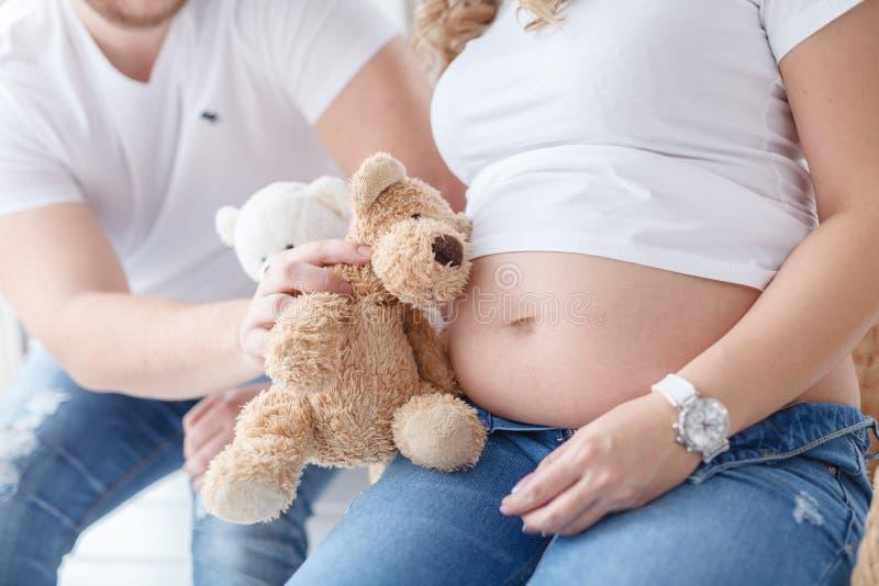 De zwangere vrouw en haar knappe echtgenoot zijn spel terwijl samen het doorbrengen van tijd royalty-vrije stock foto