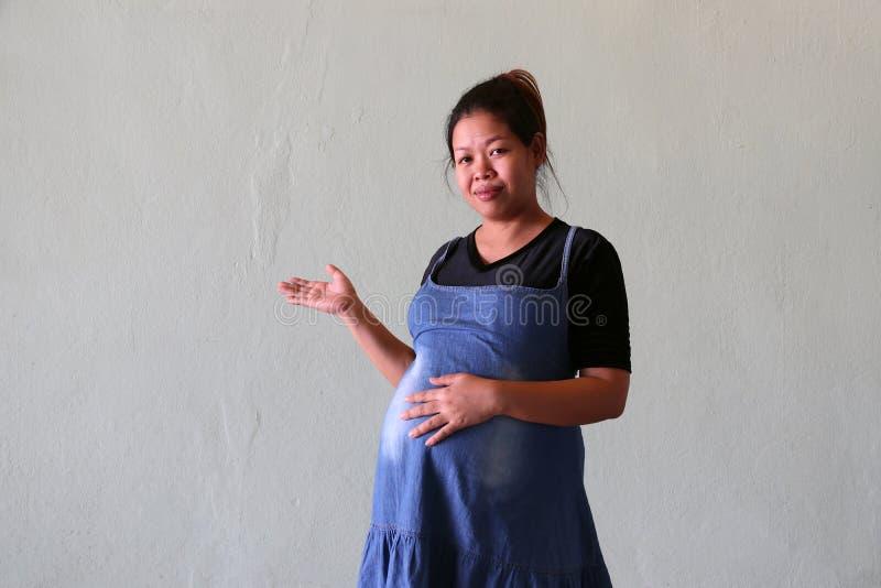 De zwangere vrouw gebruikt een denimrok of van het jeansmoederschap kleren met zwarte T-shirt, status en gegolfte rechts aan de k stock fotografie
