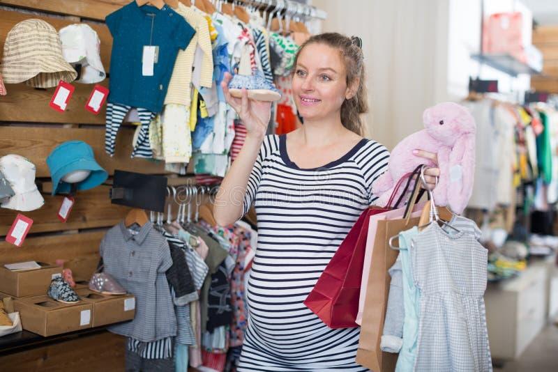 De zwangere vrouw in gestreepte uniformjas kiest schoenen voor de baby stock afbeeldingen