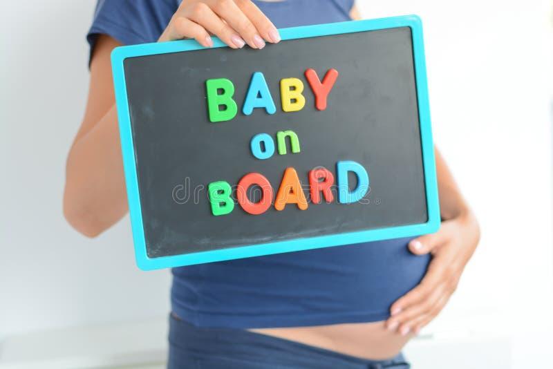 De zwangere vrouw houdt een baby aan boord van gekleurde teksten op bord over haar buik stock foto