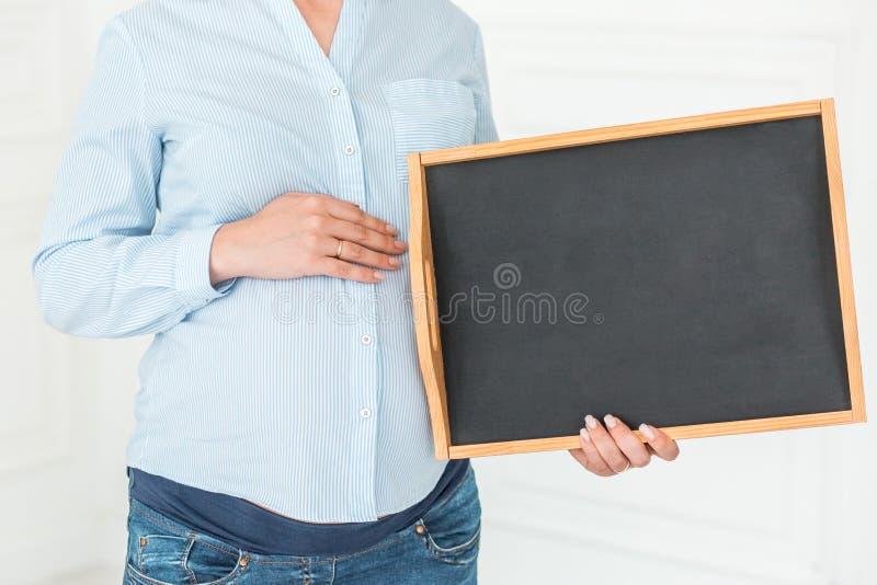 De zwangere vrouw houdt een leeg bord Close-up, exemplaarruimte, binnen stock foto