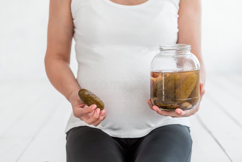De zwangere vrouw houdt gezouten komkommers in een kruik dichtbij haar buik royalty-vrije stock afbeelding