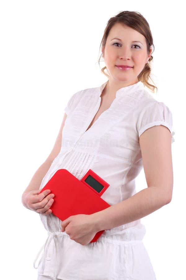 De zwangere vrouw houdt rood saldo royalty-vrije stock fotografie