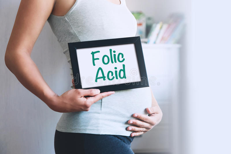 De zwangere vrouw houdt whiteboard met tekstbericht - FOLIC ZUUR royalty-vrije stock fotografie