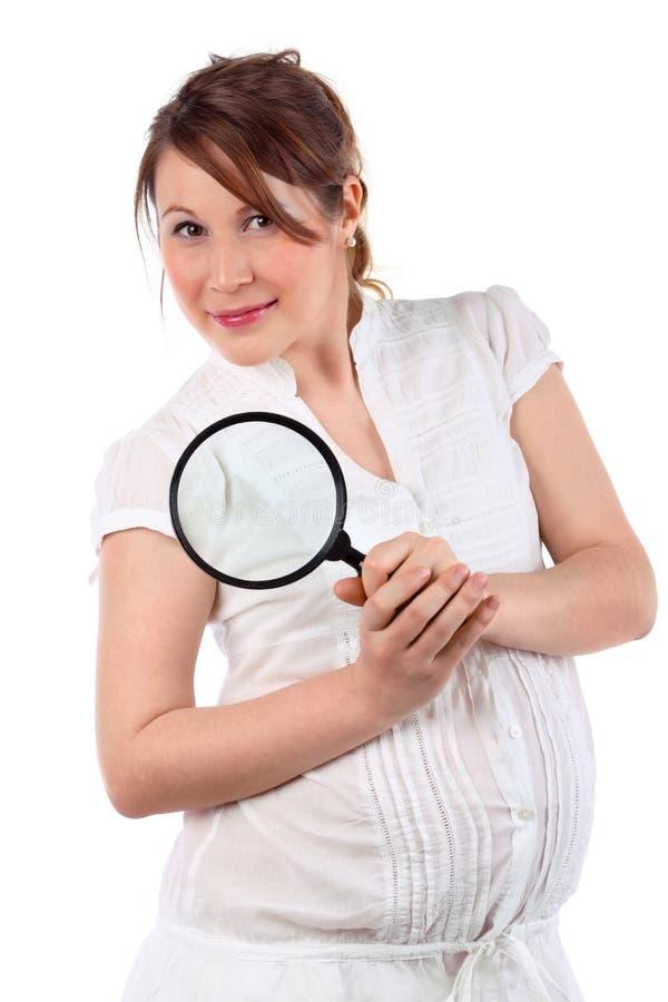 De zwangere vrouw kijkt door vergrootglas royalty-vrije stock afbeeldingen