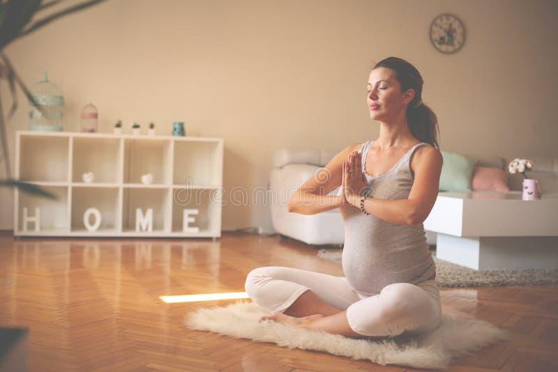 De zwangere vrouw mediteert binnen in yoga stelt Vrouw die binnen van genieten stock foto's