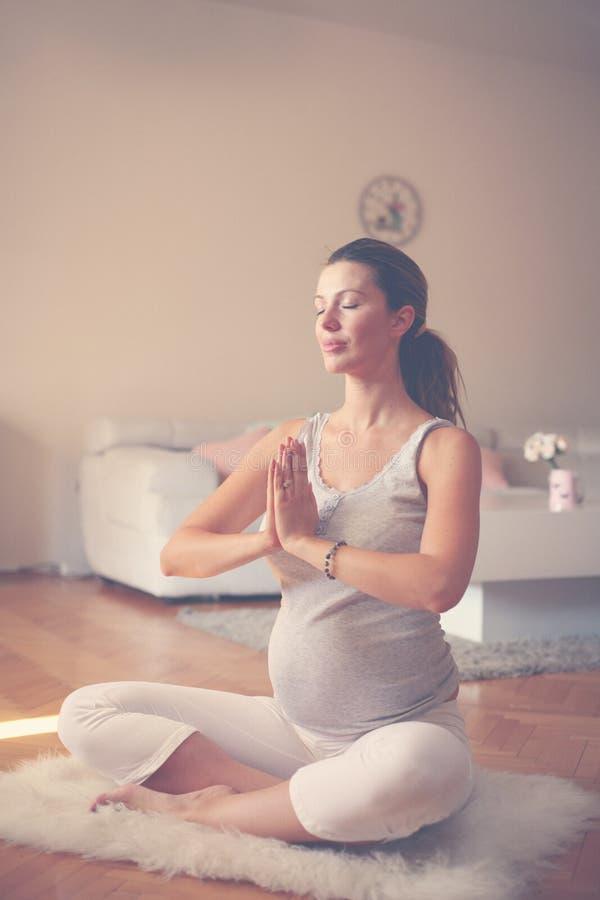 De zwangere vrouw mediteert binnen in yoga stelt Vrouw die binnen van genieten stock afbeeldingen