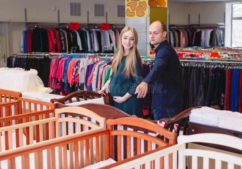 De zwangere vrouw met echtgenoot kiest een babywieg in de opslag stock foto's