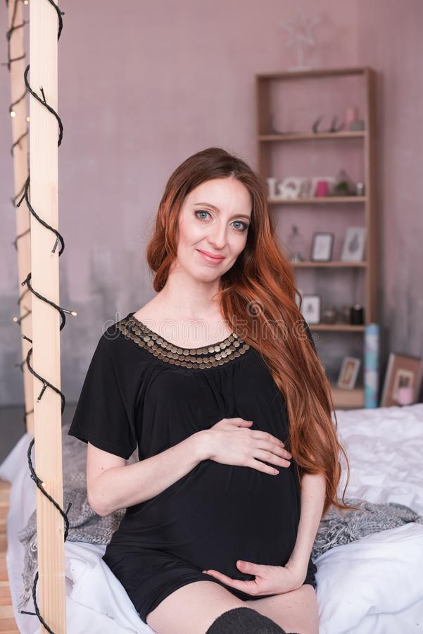 De zwangere vrouw met lang rood haar, in een zwarte kleding stock afbeelding