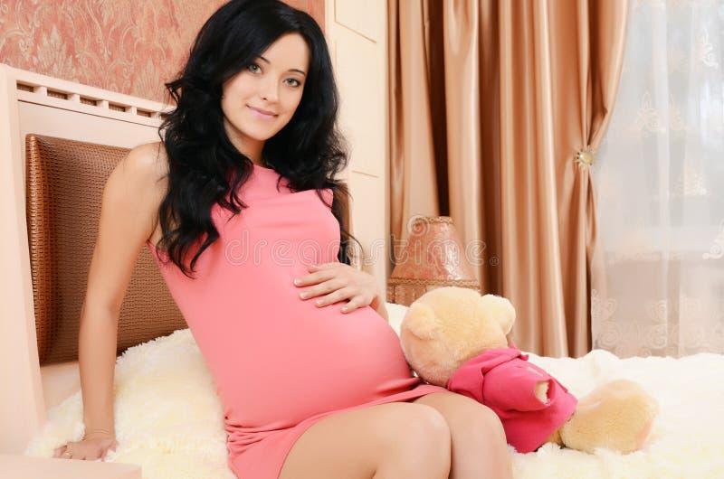 De zwangere vrouw op een bed in een ruimte royalty-vrije stock fotografie