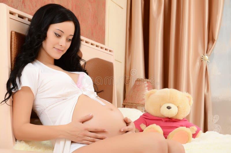 De zwangere vrouw op een bed in een ruimte royalty-vrije stock afbeeldingen