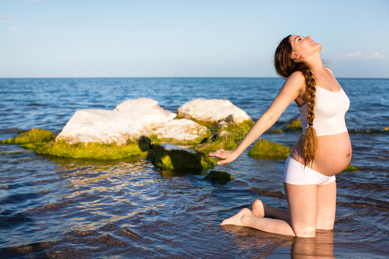 De zwangere vrouw in sportenbustehouder die oefening in ontspanning op yoga doen stelt op overzees stock foto
