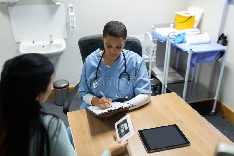 De Zwangere Vrouw van artsengiving prescription to in het Ziekenhuis stock foto's