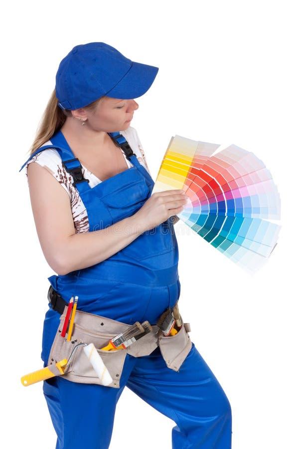 De zwangere vrouw in werkende overall stock afbeelding