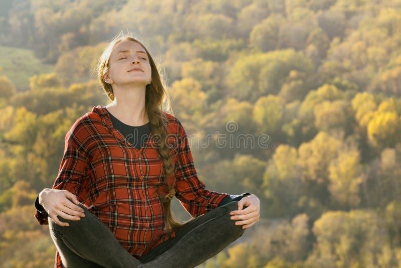 De zwangere vrouw zit op een heuvel met haar gesloten ogen meditatie royalty-vrije stock foto's