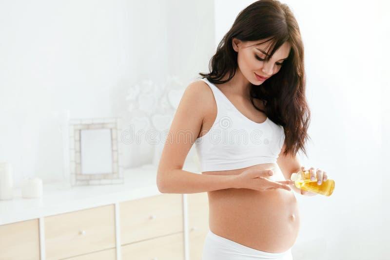 De zwangere Zorg van de Vrouwenhuid Wijfje die Olie op Buik toepassen royalty-vrije stock afbeelding