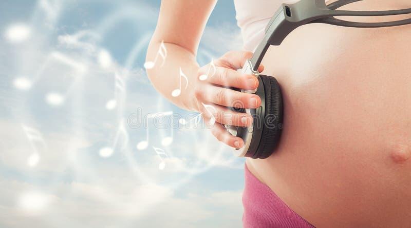 De zwangerschap en de muziek van het concept. buik van zwangere vrouw en headpho stock foto's