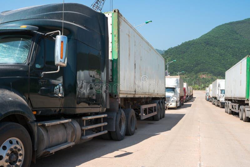 De zware die vrachtwagens laadden met goederenaanhangwagens, op wachtend gebied op staatsgrens worden geparkeerd die in Vietnam k royalty-vrije stock afbeelding
