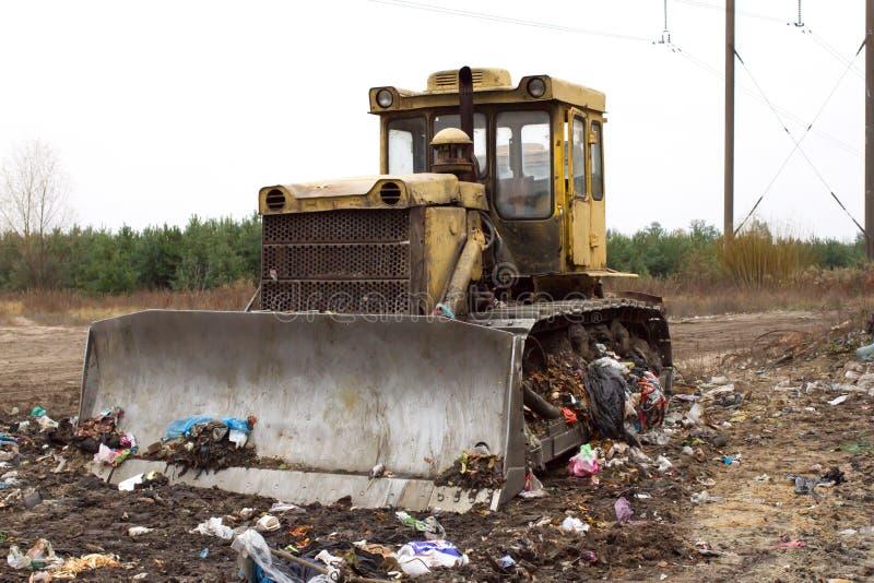 De zware gevolgde voertuigen produceert huisvuilhoop van geaborteerd plastiek in stortplaats buiten de stad stock afbeeldingen