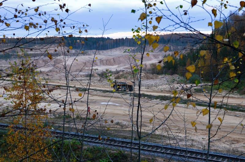 De zware grote vrachtwagen van de steengroevestortplaats Het werk van bouwmateriaal in de mijnbouw Productie nuttige mineralen royalty-vrije stock foto