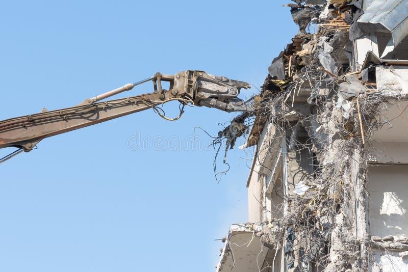 De zware pijl van materiaal hydraulische scharen ontmantelt het gebouw, vernielingsvernietiging stock foto's