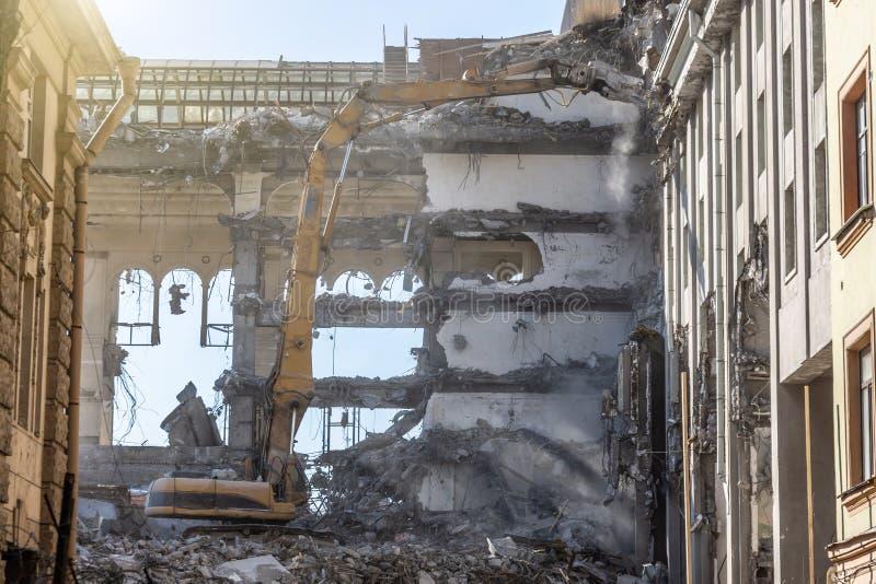De zware pijl van materiaal hydraulische scharen ontmantelt het gebouw, vernielingsvernietiging royalty-vrije stock afbeelding