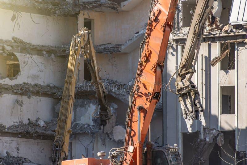 De zware pijl van materiaal hydraulische scharen ontmantelt het gebouw, vernielingsvernietiging royalty-vrije stock foto's