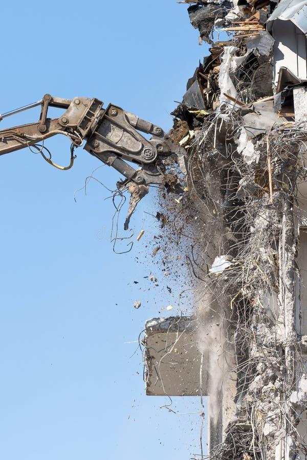 De zware pijl van materiaal hydraulische scharen ontmantelt het gebouw, vernielingsvernietiging dichtbij mening stock afbeeldingen