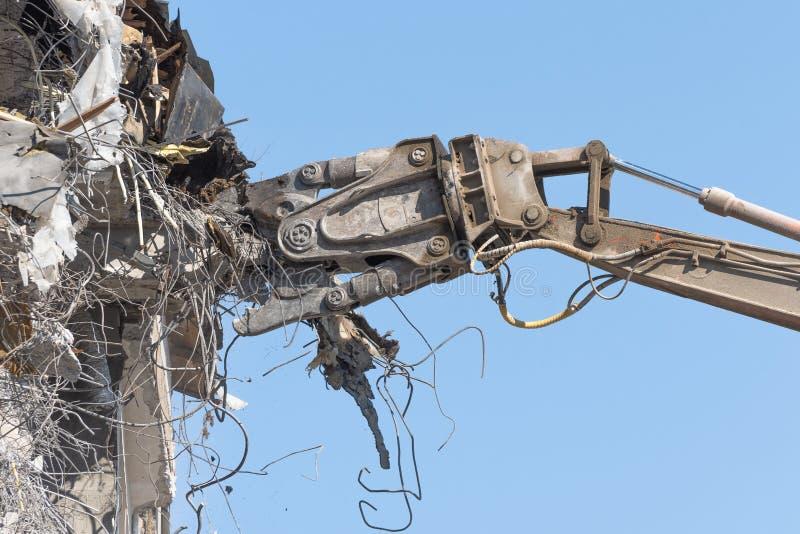 De zware pijl van materiaal hydraulische scharen ontmantelt het gebouw, vernielingsvernietiging dichtbij mening royalty-vrije stock foto