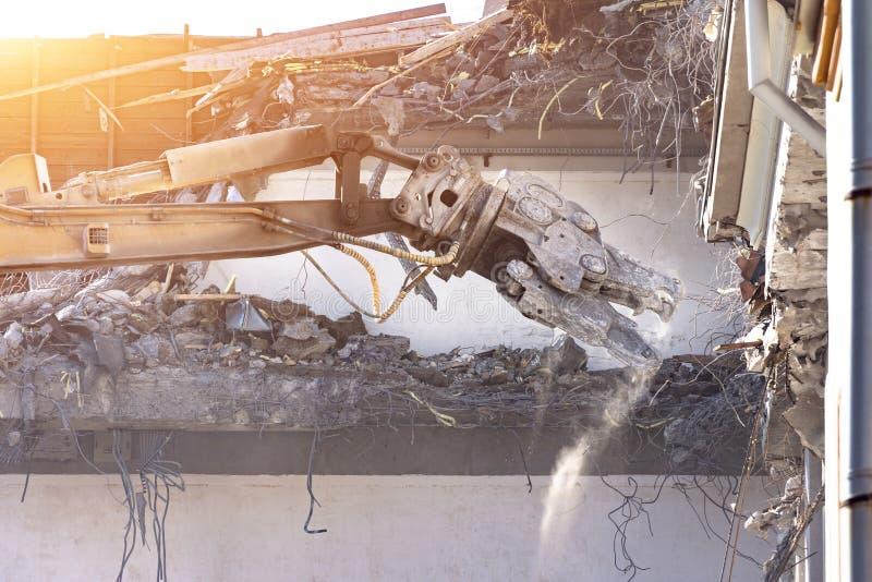 De zware pijl van materiaal hydraulische scharen ontmantelt het gebouw, vernielingsvernietiging Sluit omhoog mening royalty-vrije stock foto