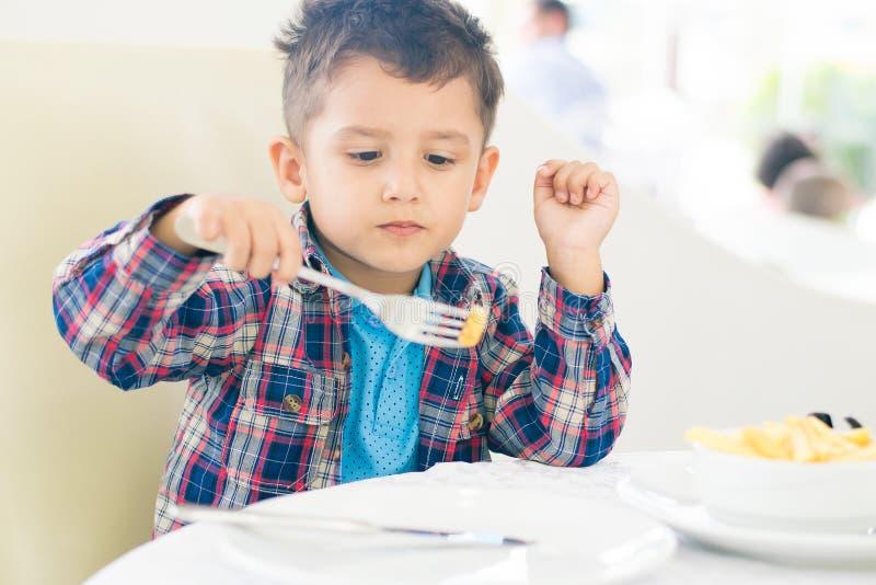 De zwart-haired jongen die bij een koffie eten royalty-vrije stock fotografie
