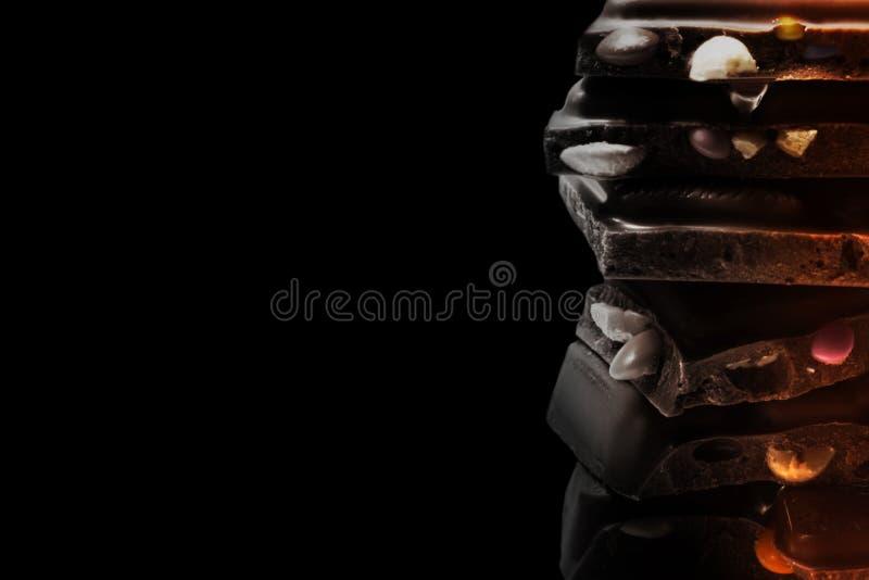 De zwart-wit chocoladetoren van diverse die delen op zwarte achtergrond worden geïsoleerd royalty-vrije stock afbeeldingen