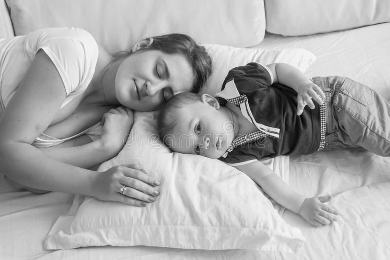 De zwart-witte foto die van de hoog puntmening van jonge moeder daarna haar babyjongen slapen die in bed liggen royalty-vrije stock afbeelding