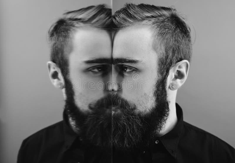 De zwart-witte foto van een mens met een baard en een modieus kapsel kleedde zich in het zwarte overhemd die zich naast de spiege stock foto's