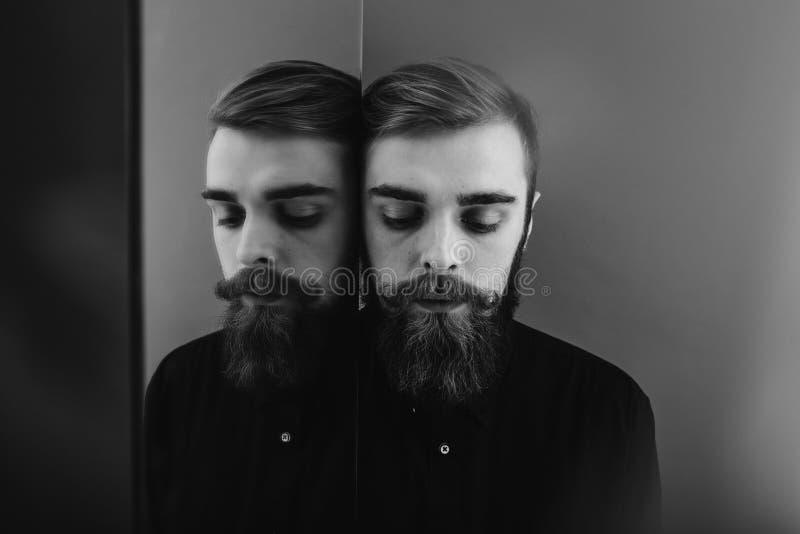 De zwart-witte foto van een mens met een baard en een modieus kapsel kleedde zich in het zwarte overhemd die zich naast de spiege stock foto
